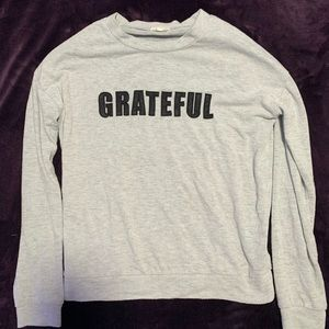 "A sweatshirt with letters ""Grateful"" in black"